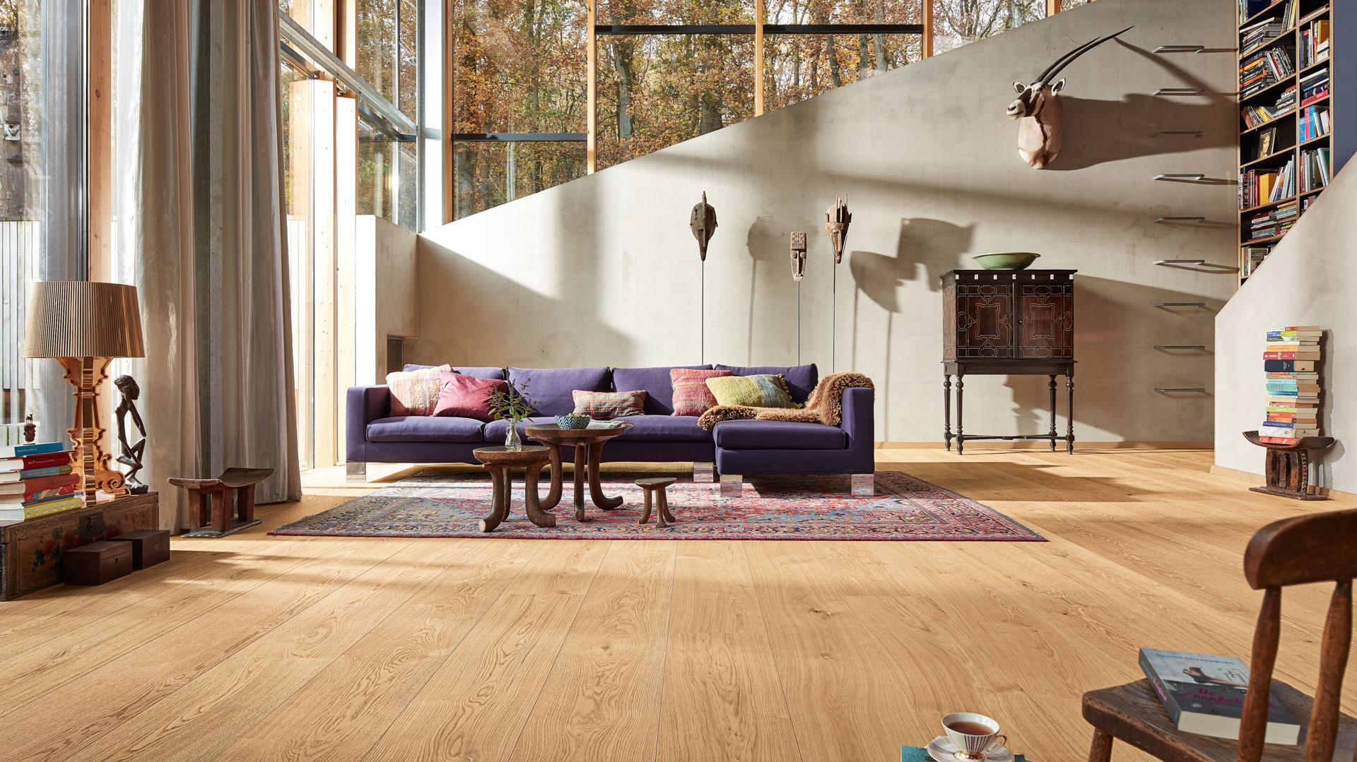 Lindura-Holzboden Eiche natur pure in einem hellen Wohnzimmer mit lila Sofa