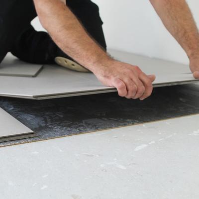 Schwimmend verlegter Parkettboden mit edelstahlfarbener Fußleiste als Detailaufnahme