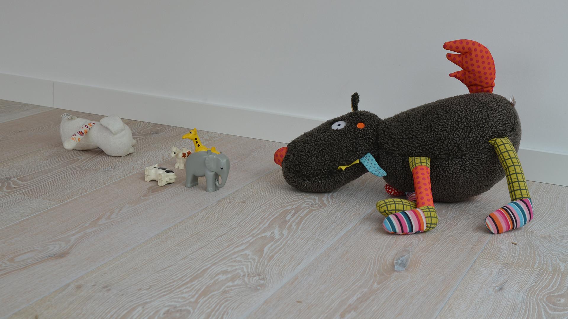 Heller Lindura-Holzboden auf dem Spielzeug und Kuscheltiere liegen