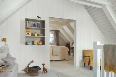Weiße Paneele an Wänden und Decke in einem Dachgeschoss